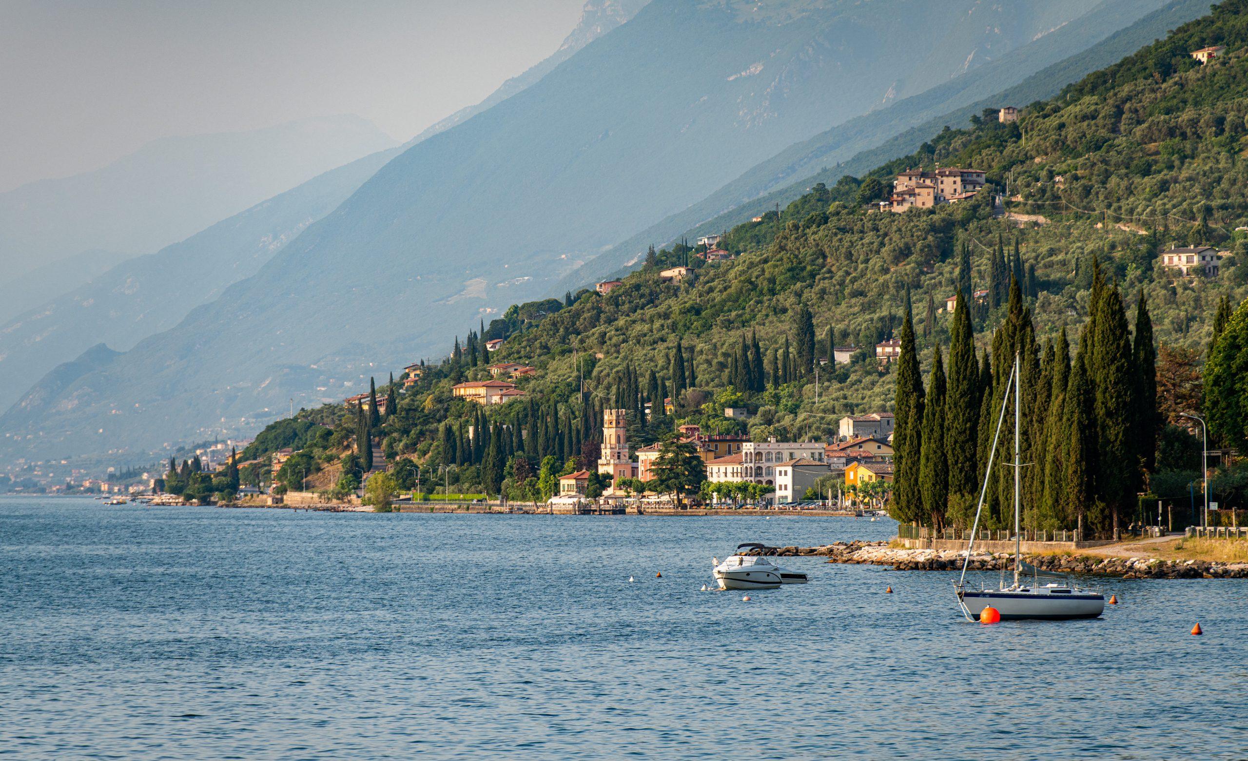Boote liegen auf dem Gardasee, in Italien. Im Hintergrund ist der Turm von Pai (La Torre di Pai) zu sehen.