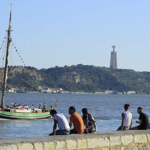 Menschen sitzen an der Küste in Cais do Sodre in Lissabon, Portugal. Wegen der starken Verbreitung der Delta-Variante des Coronavirus müssen Rückkehrer für zwei Wochen in Quarantäne.