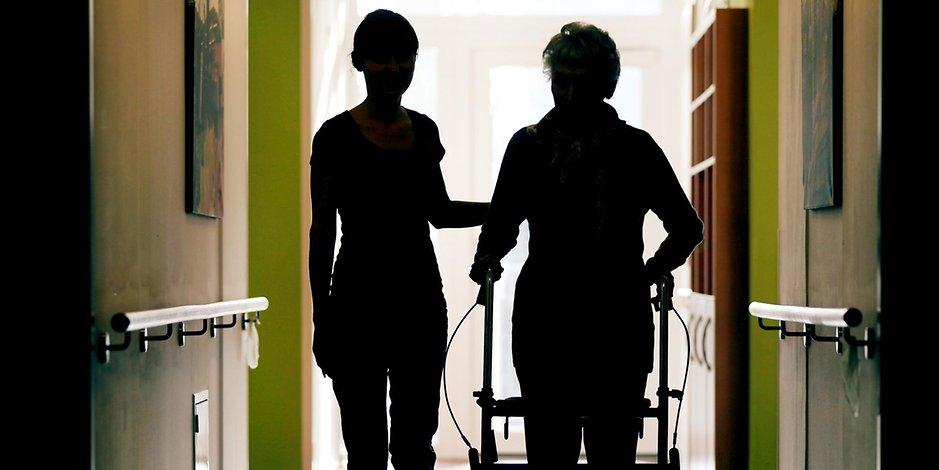 Eine Pflegerin und eine ältere Frau mit Rollator