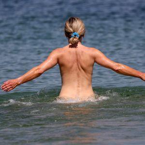 Warnemünde: Eine Frau geht an einem FKK-Abschnitt des Ostseebades ins Wasser.