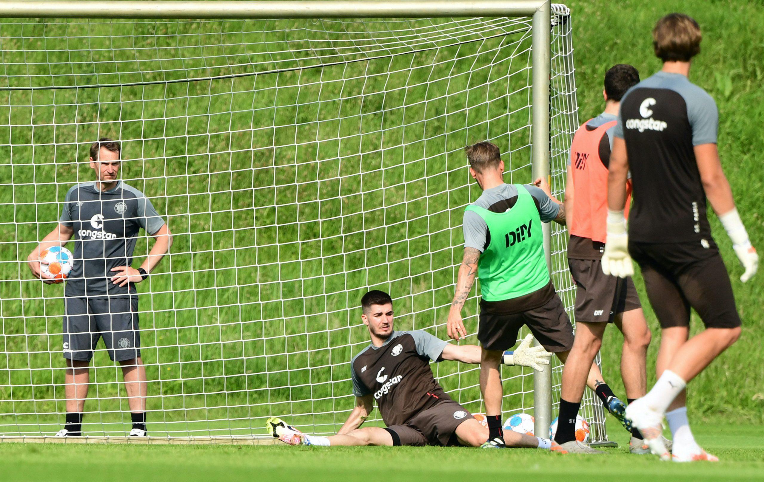 Keeper Nikola Vasilj (liegend) bekam bereits die Chance, sich zu beweisen – und allerlei Lob von Torwart-Trainer Mathias Hain (l.).