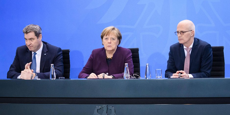 Bundeskanzlerin Angela Merkel sitzt zwischen Markus Söder (l.) und Peter Tschentscher.