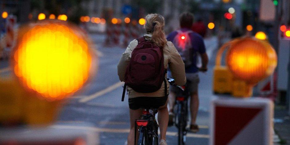 Fahrradfahrer und Baulampen.