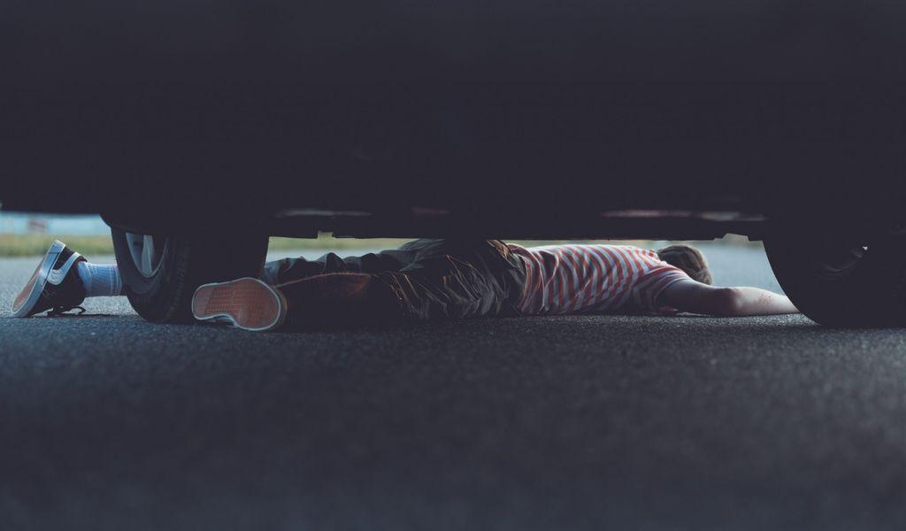 Ein Kind ist unter einem Auto eingeklemmt. (Symbolbild)