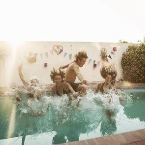 Jugendliche springen in einen Pool.