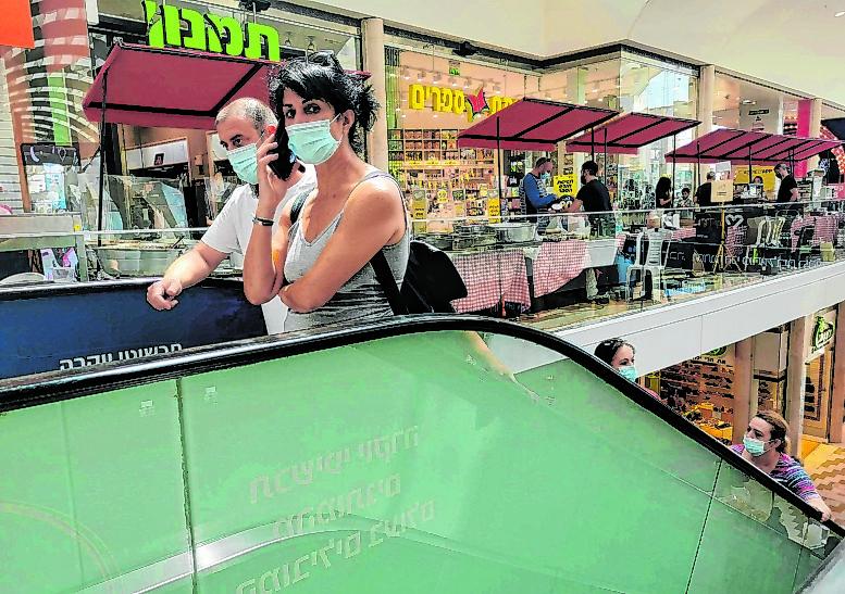 Zwei Menschen fahren mit Maske auf einer Rolltreppe in einem israelischen Einkaufszentrum