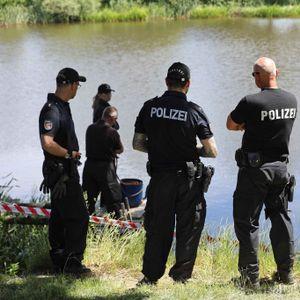 Polizisten stehen am Ufer eines Sees.