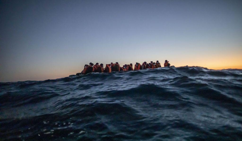 Migranten aus verschiedenen afrikanischen Nationen warten in einem Boot auf Helfer
