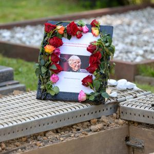 Ein blumenumrahmtes Schild mit einem Foto von Esther Bejarano steht neben ihrem Grab.