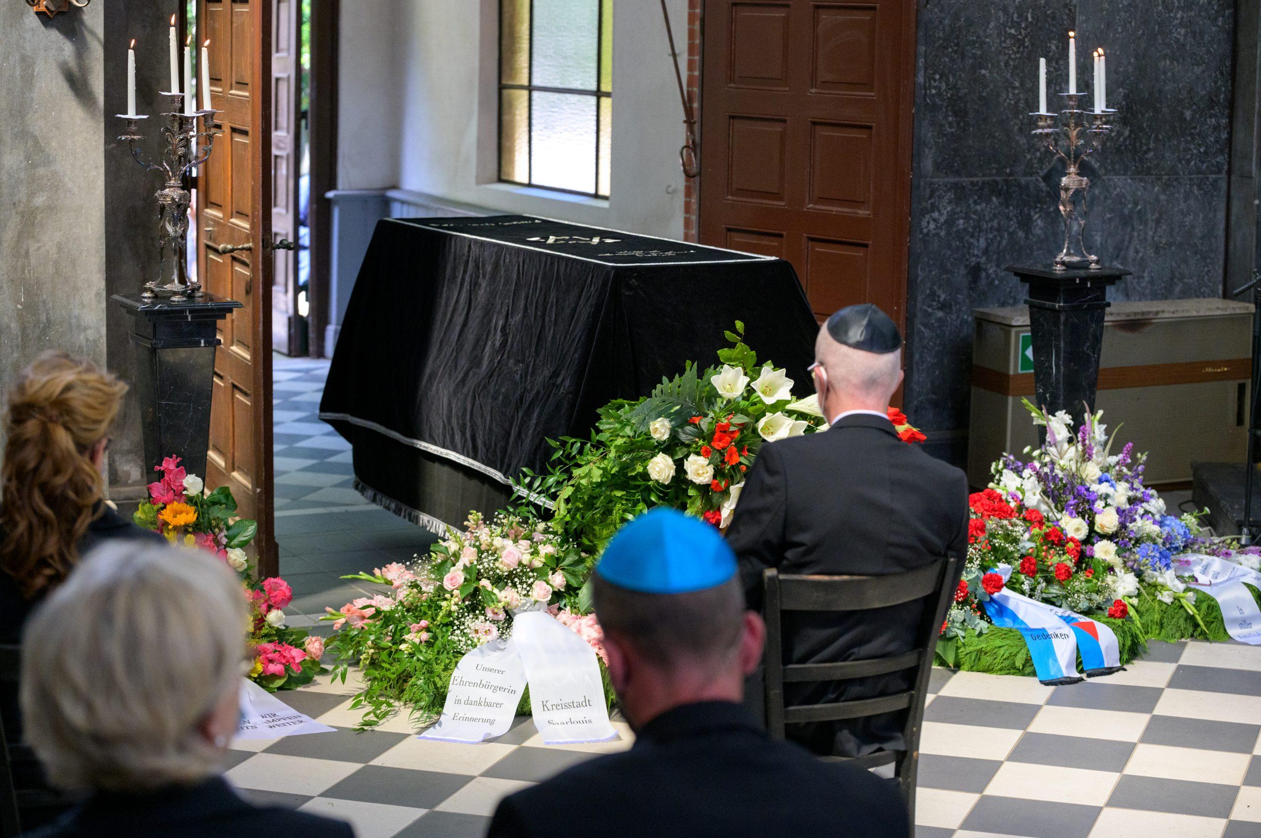 Der mit einem Tuch bedeckte Sarg von Esther Bejarano steht vor Blumenkränzen und Trauergästen in der Kapelle.