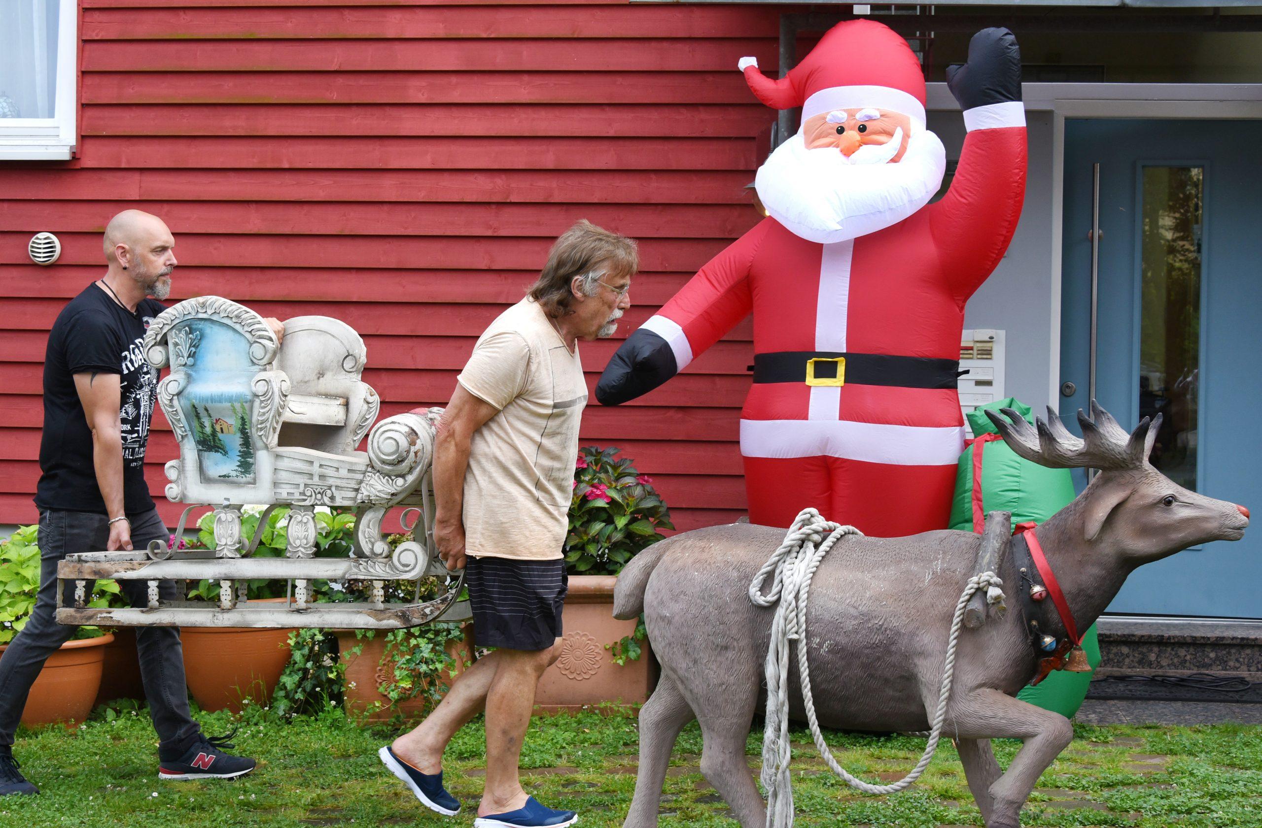 Dietmar Sawatzke und sein Sohn Sebastian tragen Weihnachtsdekoration vor den Eingang des Hauses.