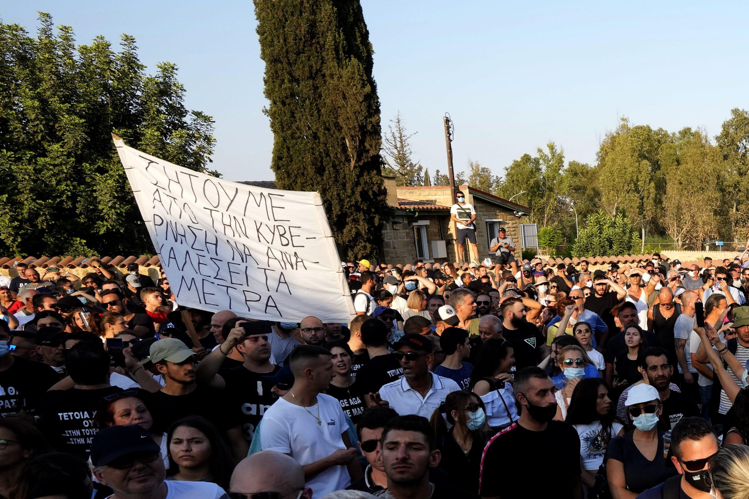 """Demonstranten halten ein Transparent, auf dem auf Griechisch steht: """"Wir fordern die Regierung auf, die Maßnahmen zurückzunehmen"""", während eines Protests gegen die Corona-Maßnahmen der Regierung vor dem Präsidentenpalast."""