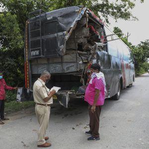 Ein Polizist macht Notizen an der Unfallstelle vor dem beschädigten Bus in Indien.