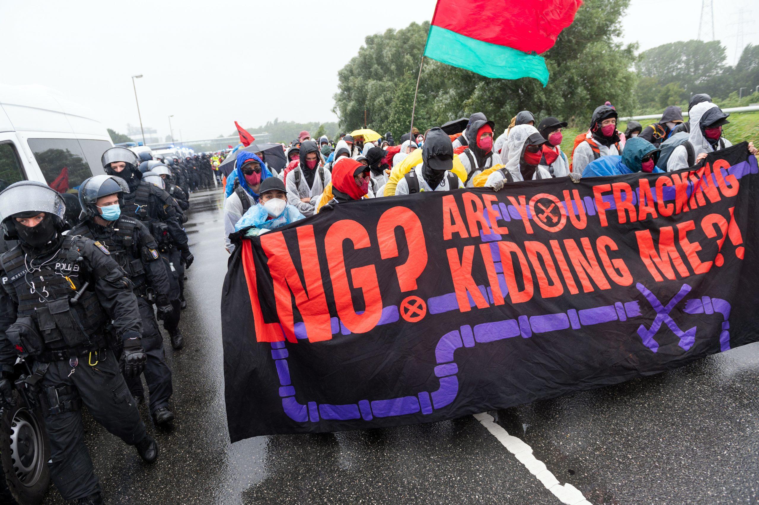 """Aktivisten gehen, begleitet von der Polizei, mit einem Plakat mit der Aufschrift """"LNG? Are you fracking kidding me?!""""."""