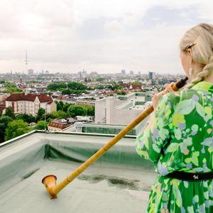 Eine Alphornspielerin auf dem Dach der Lenzsiedlung