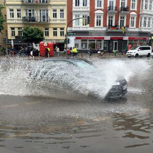 Auto fährt auf überfluteter Straße