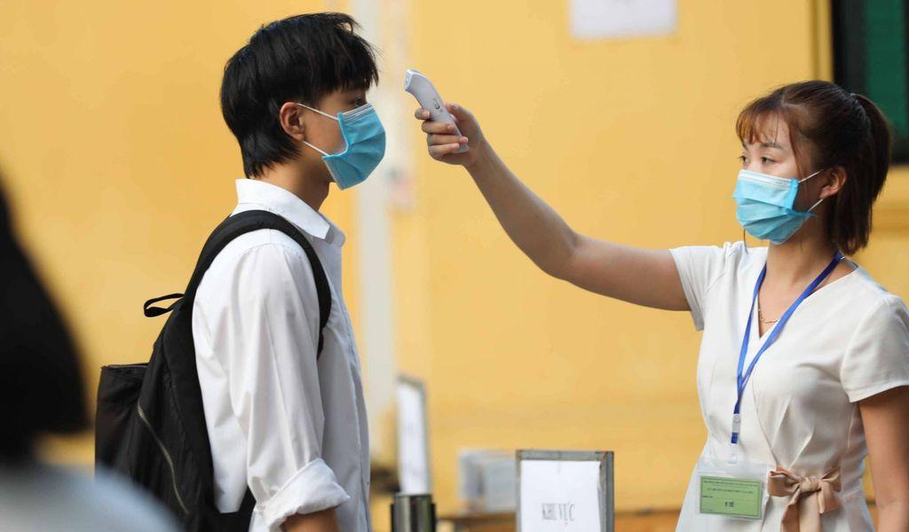 Eine medizinische Helferin misst bei einem Schüler die Temperatur.