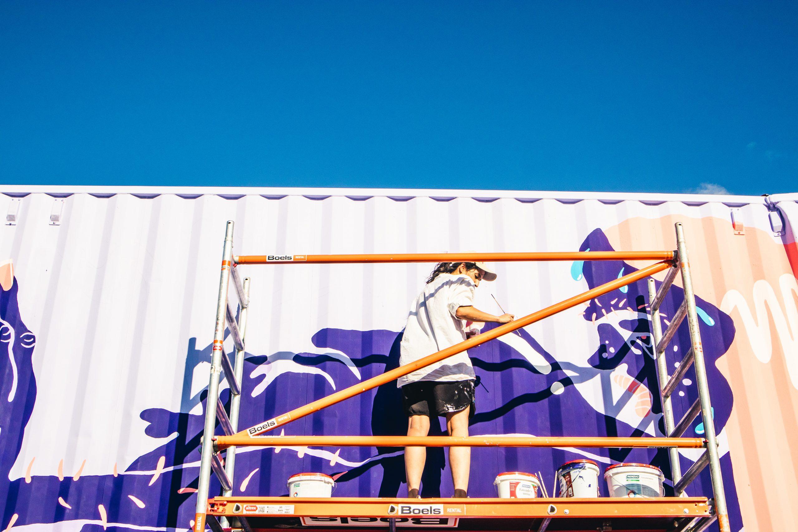 Ein Mann bemalt einen Container