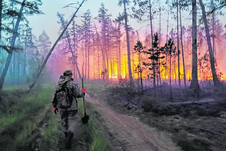 Ein Soldat geht auf einen Waldbrand in Russland zu