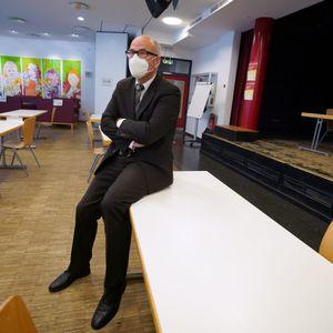 Schulsenator Ties Rabe auf einem Tisch in einem Klassenzimmer