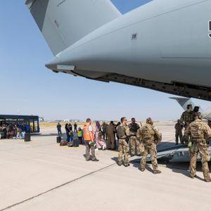 Schutzbedürftige Menschen gehen kurz nach dem Flug aus Kabul zu einem Bus.
