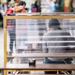 Gäste eines Restaurants warten zwischen Plexiglas-Trennscheiben auf ihre Bestellung. (Symbolbild)