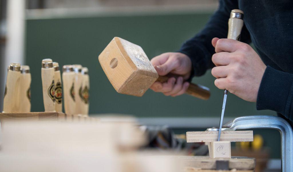 Ein Tischler in Ausbildung bei der Arbeit