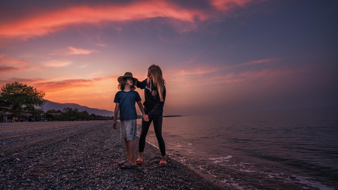 Mateo und Tanja Howe stehen während eines Sonnenunterganges an einem Strand.