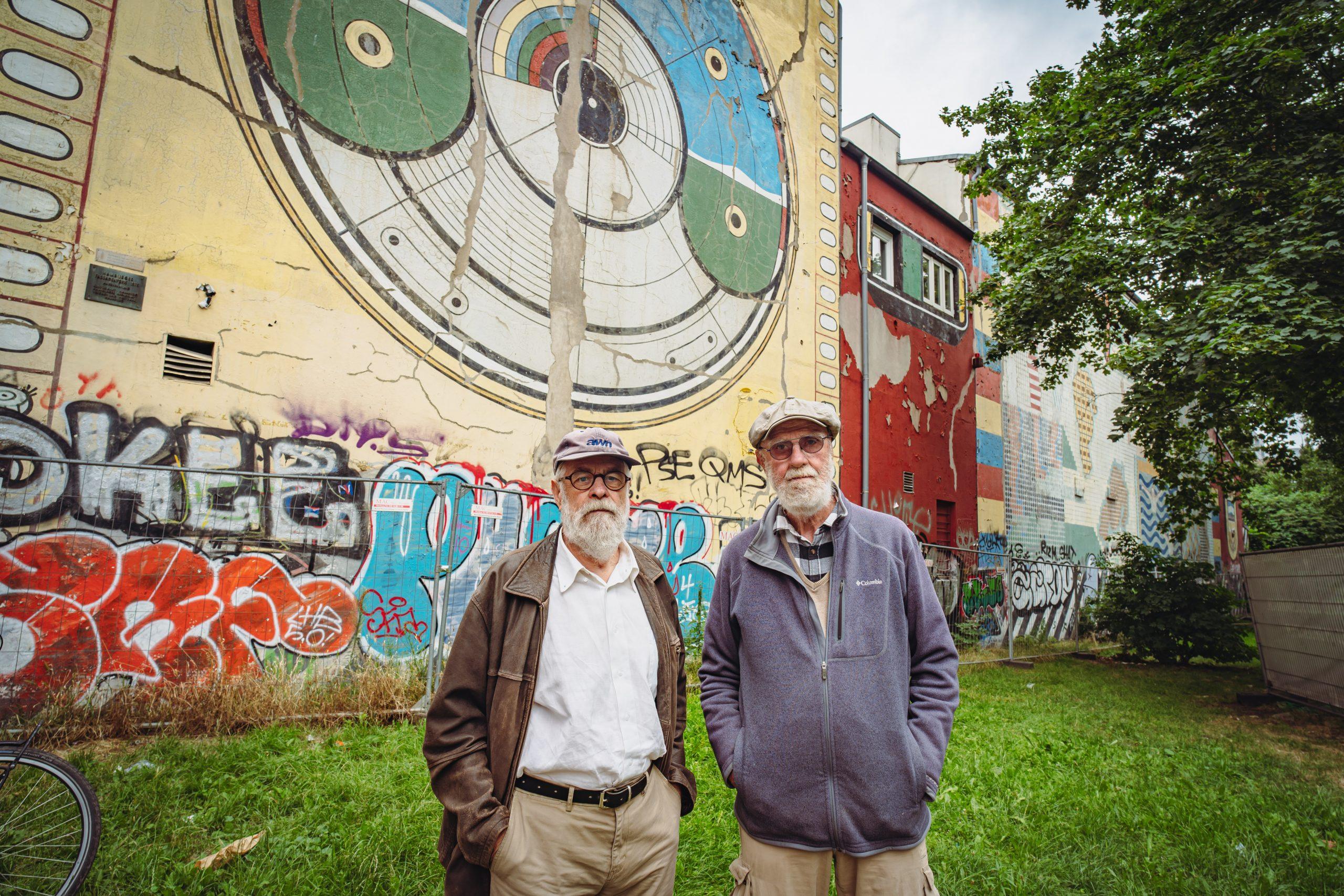 Zwei Männer stehen vor Wandgemälde