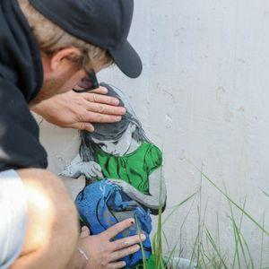 """Timm Ossege """"seiLeise"""" klebt das Bild eines Mädchens auf die Wand, das er zuvor gezeichnet hat."""