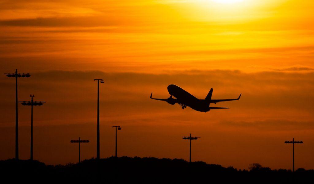 Ein Passagierflugzeug befindet sich am Flughafen von Hamburg im Steigflug vor der untergehenden Sonne.
