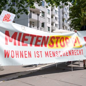 """Demonstrationsteilnehmer stehen mit einem Plakat mit der Aufschrift """"Mietenstopp - Wohnen ist Menschenrecht"""" vor einem Hochhaus."""