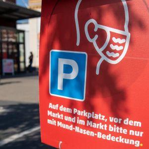 """""""Auf dem Parkplatz, vor dem Markt und im Markt bitte nur mit Mund-Nasen-Bedeckung"""" steht auf einem Hinweisschild vor einem Supermarkt."""