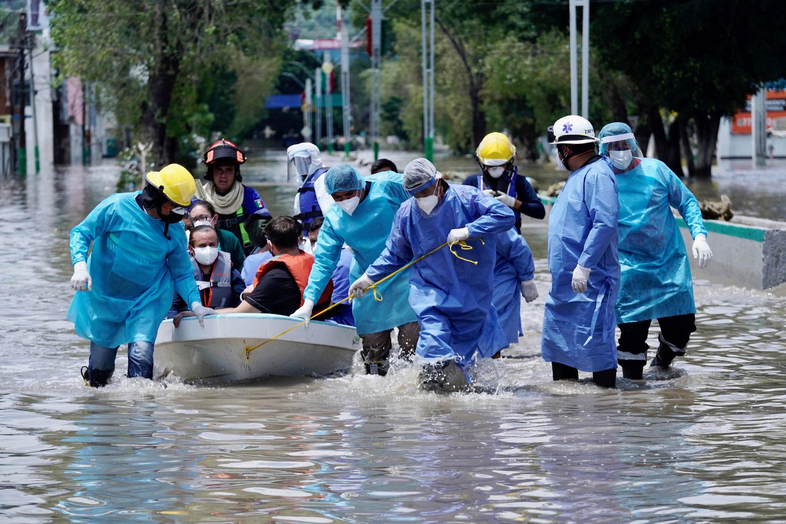 Menschen werden in einem Boot aus den Fluten gerettet (Symbolbild).