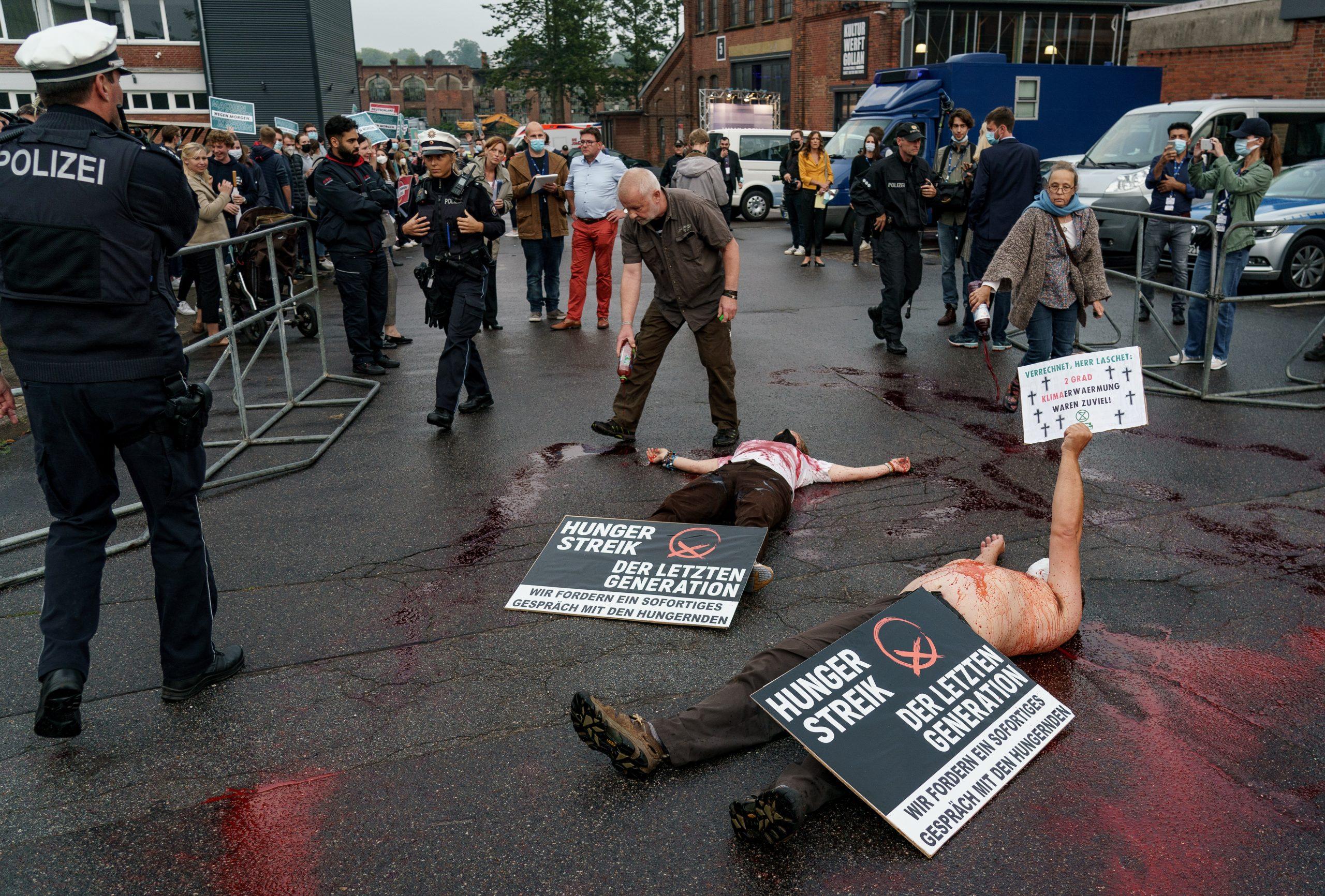 Die Klimaaktivisten bedeckten sich mit Plakaten