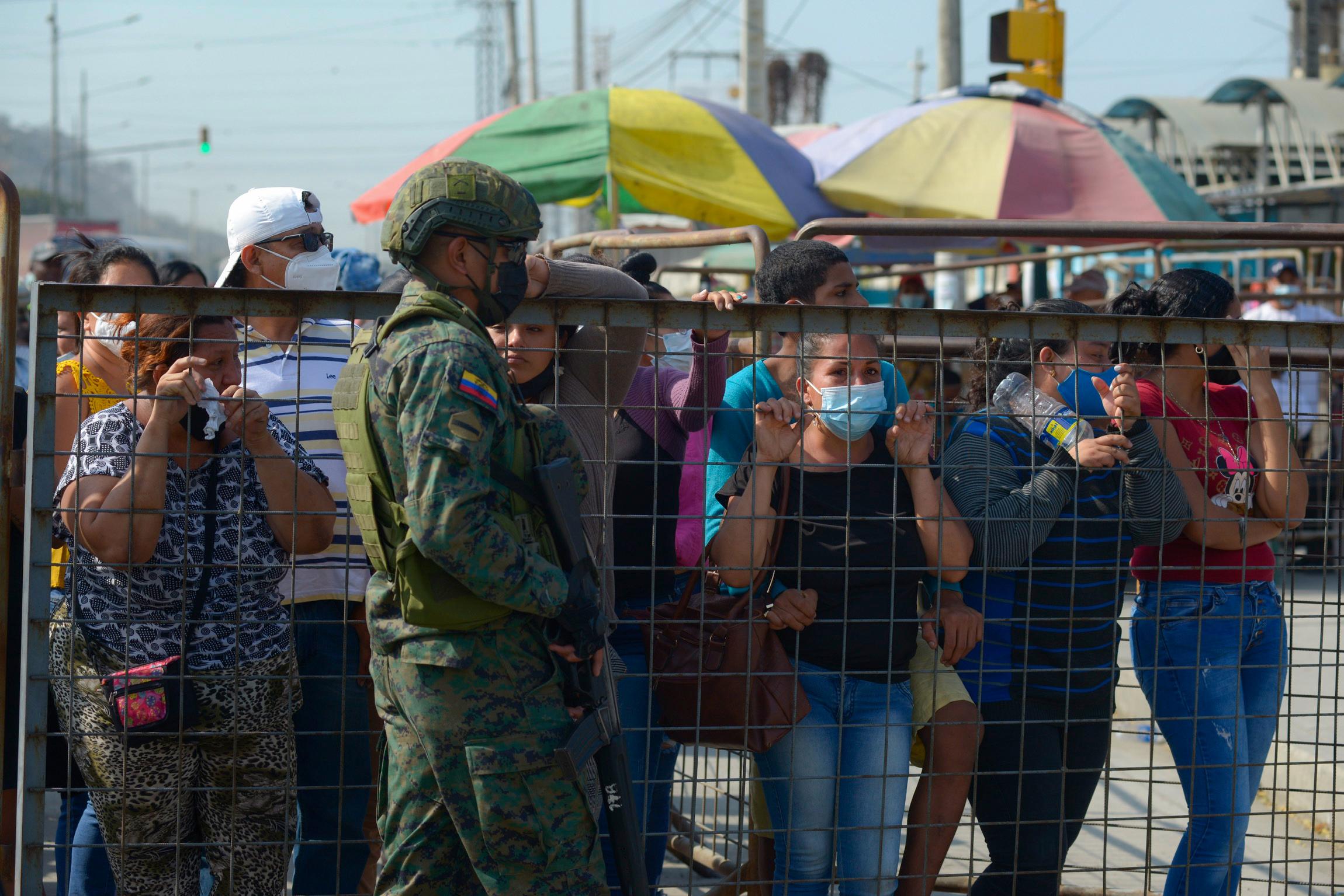 Menschen stehen am Zaun, ein bewaffneter Mann bewacht das Gelände