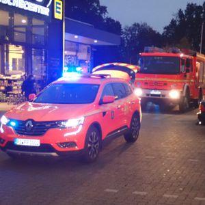 Rettungsfahrzeuge stehen auf einem Parkplatz vor dem Supermarkt