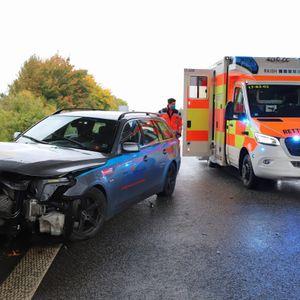 Ein Rettungswagen steht hinter dem zerstörten Unfallfahrzeug.