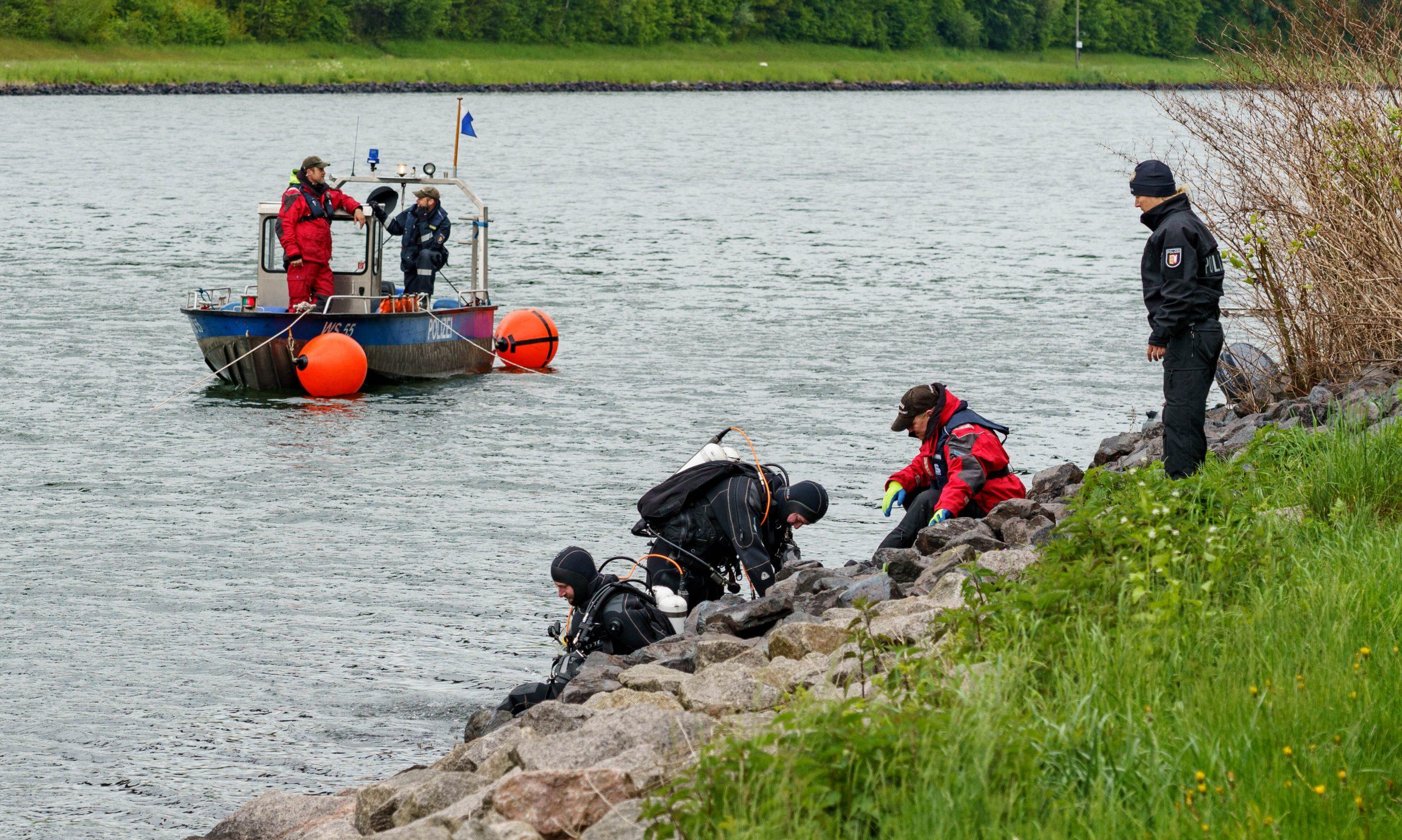 Taucher der Polizei steigen in den Nord-Ostseekanal ein.