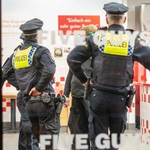 """Polizisten kontrollieren den Burger-Laden """"Five Guys"""" in Hamburg."""