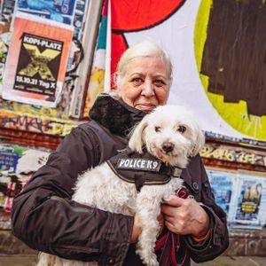Ines steht mit ihrem Hund vor dem Plakat, dessen Aufschrift mit schwarzer Farbe übermalt ist